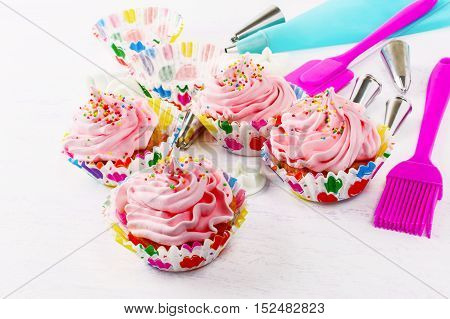 Cupcakes with pink whipped cream swirl and confectionery syringe. Birthday cupcake with pink whipped cream. Homemade decorated cupcakes.
