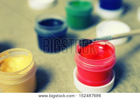 small jars with colorful gouache paints to paint and brush