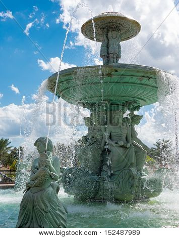Stone Fountain Statue of a green woman holding a large fish