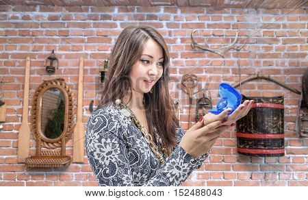 Beautiful young girl looking at a black pearl