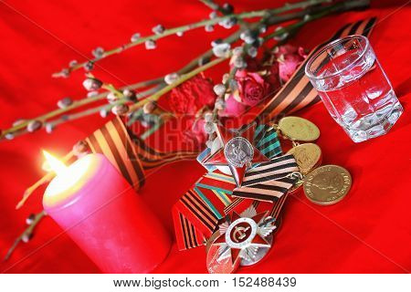 the composition of the old military decorations on a red satin cloth with a branch of a willow