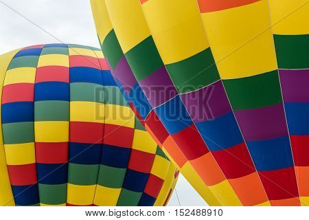 One Colorful Balloon in front of a second one against an almost white cloud filled sky.