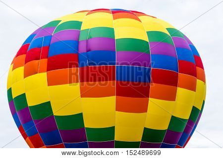 The top portion of a colorful hot air balloon against an almost white cloud filled sky.
