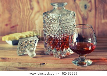 glass with sustained strong alcohol brandy on a wooden table