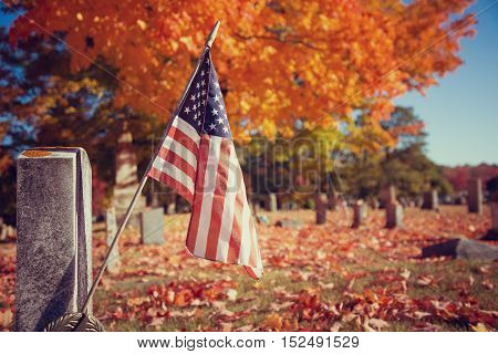 American veteran flag in autumn cemetery. Vintage filter effects.