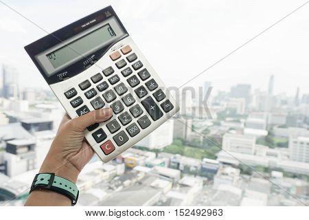 businesswoman wearing watch hold big calculator in hand