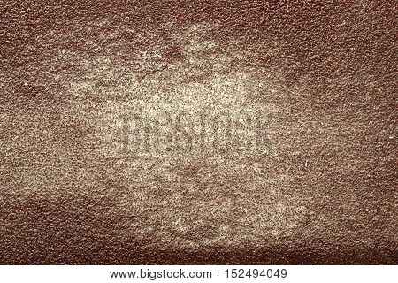 Designer background from shabby coarse sandpaper with the remnants of the light wood dust