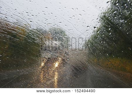 Raindrops on the windshield of the car.