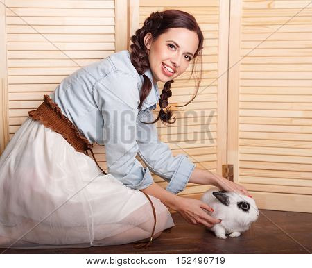 Nice girl with a rabbit in his arms. Pets. Love to the animals. Funny animals.