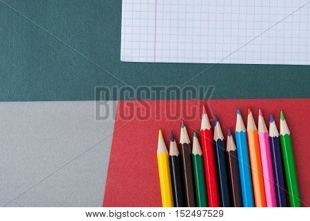 olorful pencils with eraser on green and red background. School supply