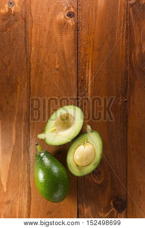 Fresh green avocado on a wooden background