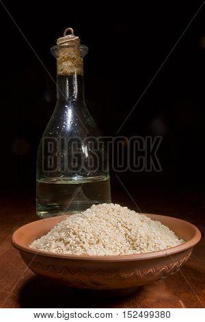 Sesame seeds and sesame oil on a dark background