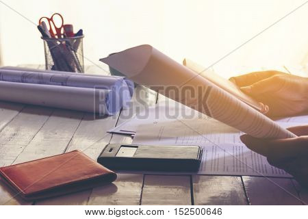 Woman Reading documents in her hands with equipment on wooden white table and sunshine.