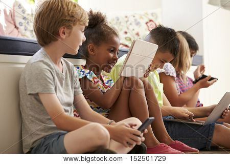 Group Of Children Sit On Floor And Use Technology