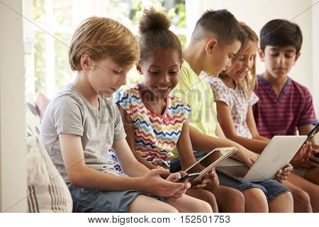Group Of Children Sit On Window Seat And Use Technology