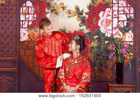 Mixed Race Bride and Groom in Studio wearing traditional Chinese wedding outfits