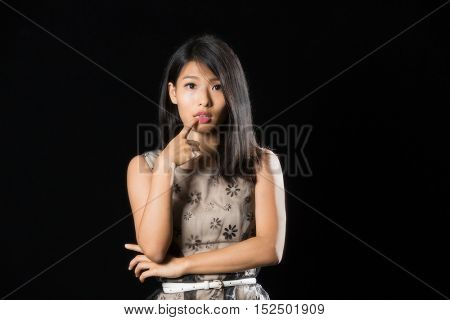 Pretty chinese girl with finger on her lip standing against black background