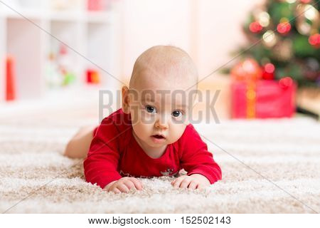 Cute baby boy lying on tummy in front of Christmas tree