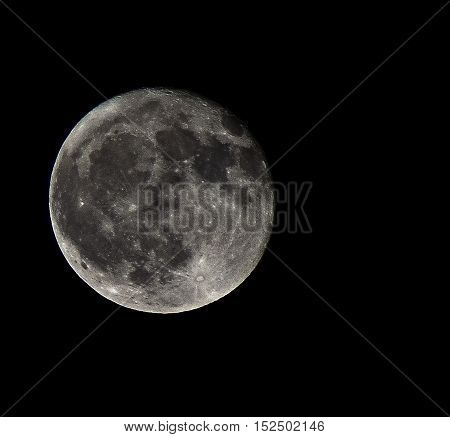 silvery full moon in the black sky and the dark
