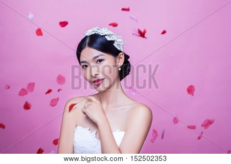 Portrait of beautiful bride with rose petals in mid-air against pink background