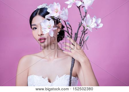 Portrait of confident bride holding artificial flowers against pink background