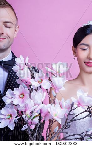 Smiling wedding couple with artificial flowers standing with eyes closed against pink background
