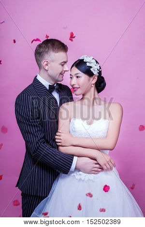 Elegant wedding couple embracing while standing against pink background