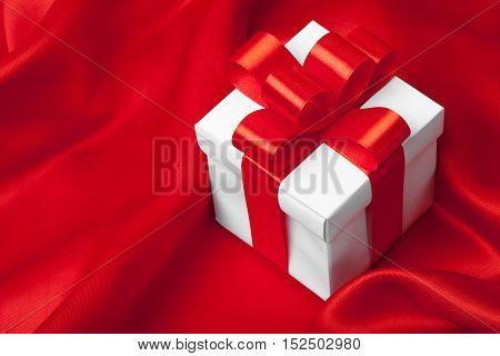 gift on red satin background. studio shot