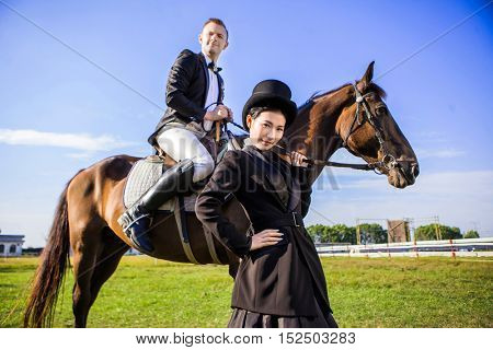 Portrait of confident woman standing by man sitting on horse at field