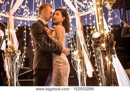 Romantic couple embracing in illuminated gazebo at night