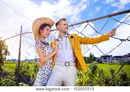 Thoughtful couple standing by fence on field against sky