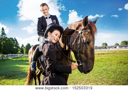 Thoughtful woman standing by man sitting on horse at field