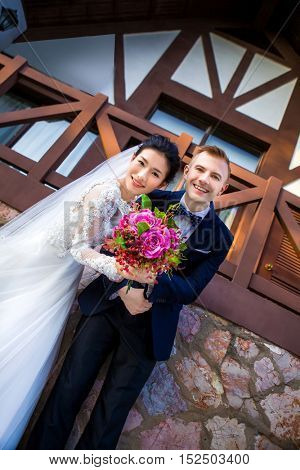 Low angle portrait of happy wedding couple holding flower bouquet against house
