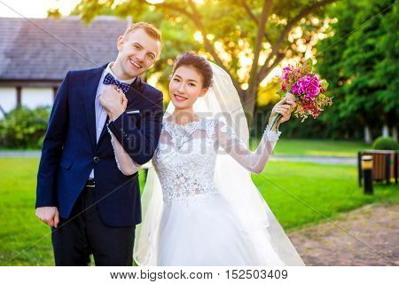 Portrait of happy wedding couple holding hands while standing at lawn