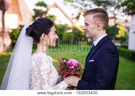 Side view of smiling wedding couple holding bouquet at lawn