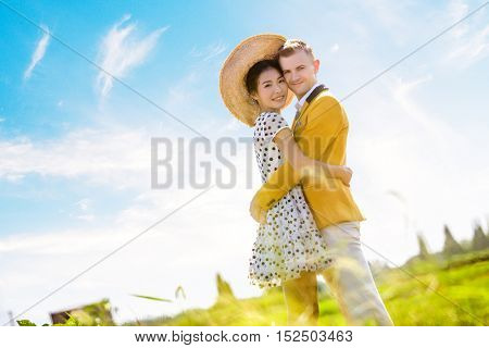 Side view portrait of romantic couple embracing on field against sky