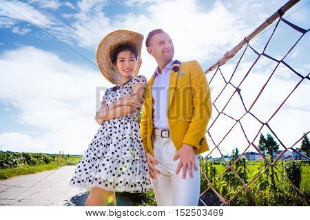 Portrait of confident woman standing with man on field against sky