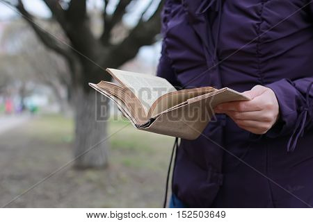 woman with book reading outdoor in a perk winter season