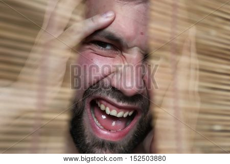 young bearded man looking through a crack in the blinds depicting emotions