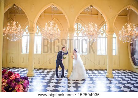 Side view of romantic wedding couple looking at each other in church