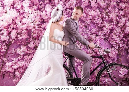 Wedding couple looking at each other against wall covered with pink flowers