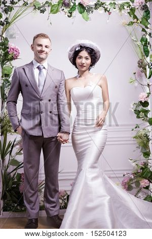 Portrait of confident wedding couple standing against white wall
