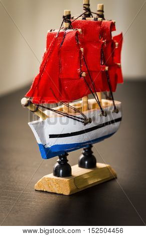 Statuette of the ancient sailing ship with red sails close-up.