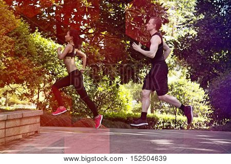 Side view of Multi ethnic couple running in park