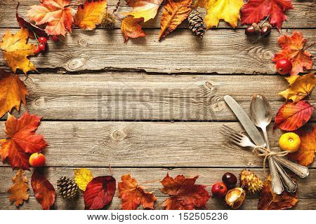 Vintage autumn border from fallen leaves and fruits with vintage silverware on wooden table. Thanksgiving autumn background