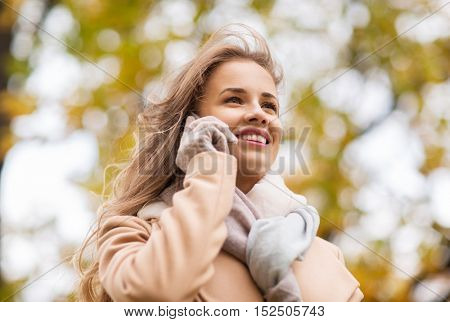 season, technology, communication and people concept - beautiful young woman in autumn park calling on smartphone