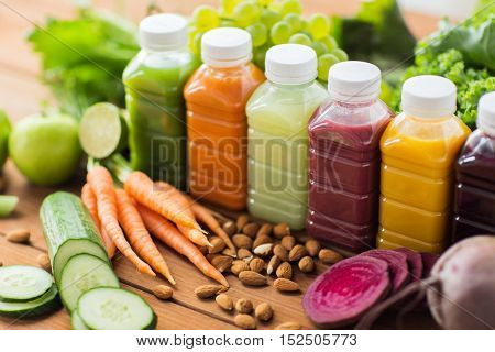 healthy eating, drinks, diet and detox concept - plastic bottles with different fruit or vegetable juices and food on wooden table