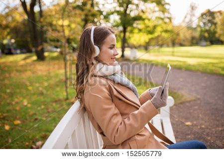 season, technology and people concept - beautiful happy young woman with tablet pc computer and headphones listening to music and sitting on bench in autumn park