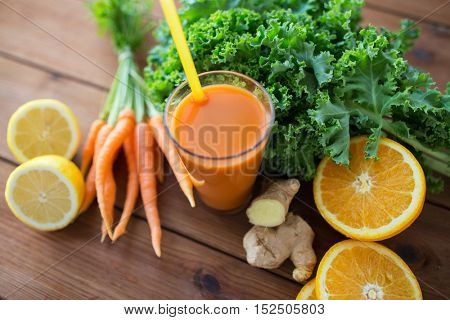 healthy eating, food, dieting and vegetarian concept - glass of carrot juice, fruits and vegetables on wooden table