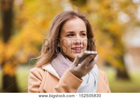 season, technology and people concept - beautiful young woman walking in autumn park and using voice command recorder on smartphone